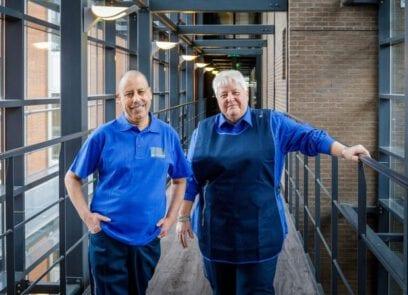 Foto waarop twee medewerkers van de rijksschoonmaakorganisatie lachend naar de camera kijken