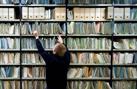 foto man voor archiefkasten