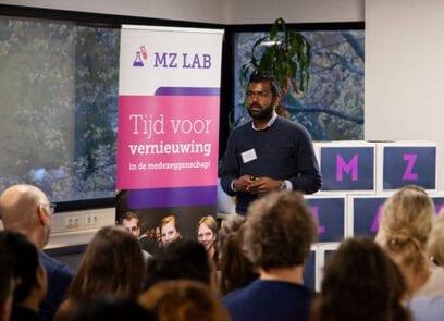 Man op podium kijkt richting publiek, met banner van MZ lab Rijk op achtergrond