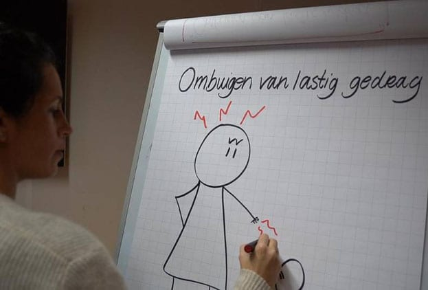 Vrouw schrijft op whitepaper 'ombuigen van lastig gedrag' met een gefrustreerd getekend poppetje eronder