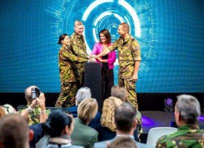 Staattsecretaris Barbara Visser staat op podium en druk met 3 defensiemedewerkers de handen op een knop