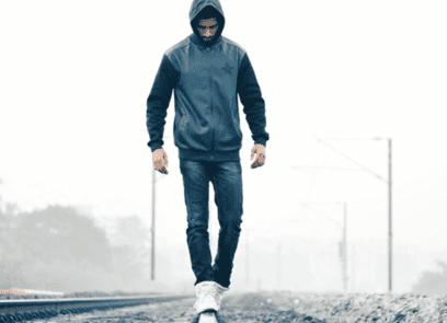 Vooraanzicht mannelijke figuur met een capuchon op, die balanceert op spoorwegrails