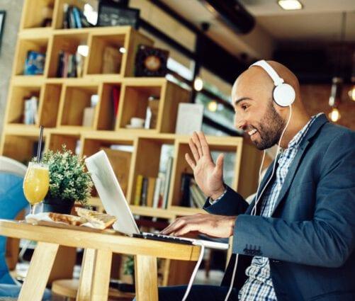 rijksmedewerker met hoofdtelefoon op zwaait naar laptopscherm tijdens beeldbellen