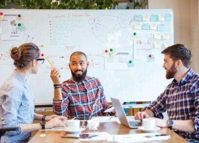 drie personen aan tafel met laptop met elkaar in overleg, op achtergrond whiteboard met aantekeningen