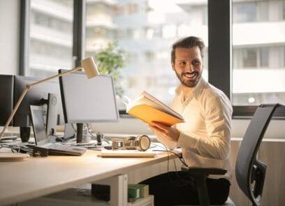Rijksmedewerker lachend achter zijn bureau