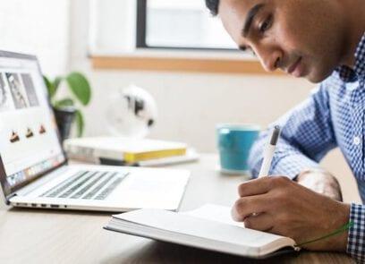 Zij-aanzicht van persoon aan tafel die schrijft in een boekje en voor zich een laptop opengeklapt heeft staan.