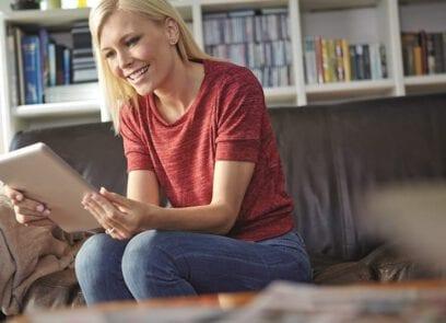 Vrouw zit op bank en kijkt lachend naar de tablet die zij in haar handen houdt.