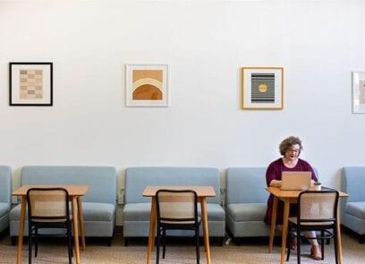 werkende vrouw achter een laptop in een bedrijfsrestaurant